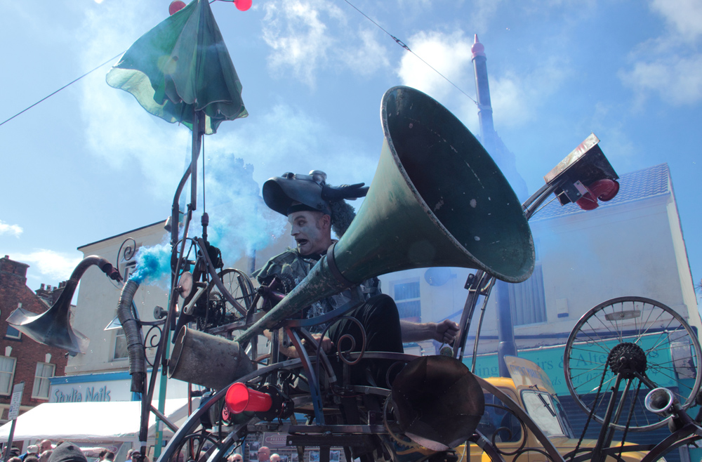close up of the hurly burly mobile sound sculpture with performer and blue smoke at Spare Parts Festival Parade 2015