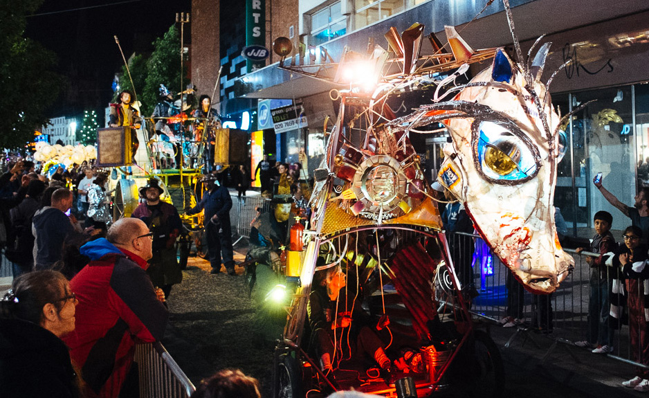 Junk dragon puppet and boneshaker human powered vehicle in night time procession, Preston 2016